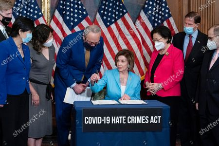 Speaker of the House Nancy Pelosi, D-Calif., accompanied from left by Rep. Don Beyer, D-Va., Rep. Judy Chu, D-Calif., Rep. Grace Meng D-N.Y., Senate Majority Leader Chuck Schumer, D-N.Y., Sen. Mazie Hirono, D-Hawaii, Sen. Richard Blumenthal, D-Conn., and Rep. Jerrold Nadler, D-N.Y., during the signing ceremony of the COVID-19 Hate Crime Act, on Capitol Hill in Washington, Wednesday