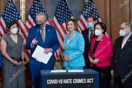 Senate Majority Leader Chuck Schumer, D-N.Y., accompanied by Speaker of the House Nancy Pelosi, D-Calif., Rep. Grace Meng D-N.Y., Sen. Mazie Hirono, D-Hawaii, Sen. Richard Blumenthal, D-Conn., and Rep. Jerrold Nadler, D-N.Y., speaks during the signing ceremony of the COVID-19 Hate Crime Act, on Capitol Hill in Washington, Wednesday