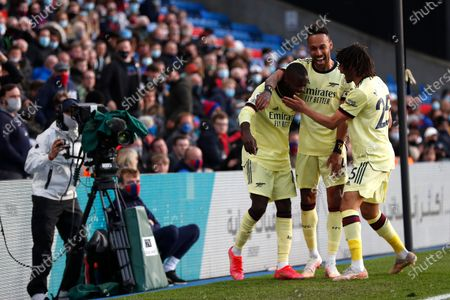 Stock Photo of Arsenal's Nicolas Pepe, left, celebrates with Arsenal's Pierre-Emerick Aubameyang, center, and Arsenal's Mohamed Elneny after scoring his side's opening goal during the English Premier League soccer match between Crystal Palace and Arsenal, at Selhurst Park in London, England