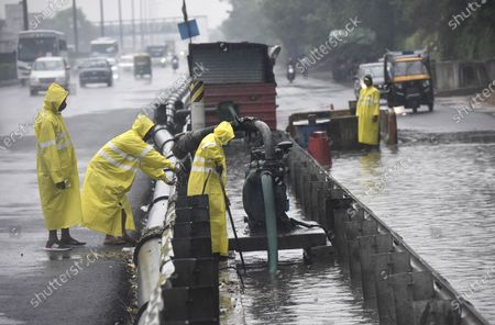 MCG workers pumping water out of a waterlogged service road at Narsinghpur along NH48 during a rainy day, on May 19, 2021 in Gurugram, India. India Meteorological Department (IMD) scientists said Delhi is also likely to receive heavy to very heavy rainfall on Wednesday. An advisory issued by the IMD said Tauktae and its remnants would interact with a western disturbance trough, creating an interaction zone.