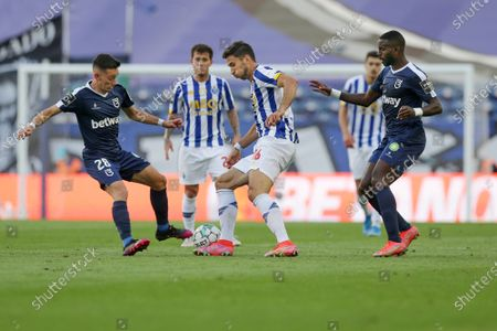 FC Porto's Marko Grujic (C) in action against Belenenses SAD's Afonso Sousa (L) and Silvestre Varela (R) during their Portuguese First League soccer match at Dragao stadium, Porto, Portugal, 19 May 2021.
