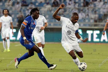 Al-Hilal's player Bafetimbi Gomis (L) in action against Al-Ahli's Motaz Hawsawi (R) during the Saudi Professional League soccer match between Al-Hilal and Al-Ahli at Prince Faisal Bin Fahd Stadium, Riyadh, Saudi Arabia, 19 May 2021.