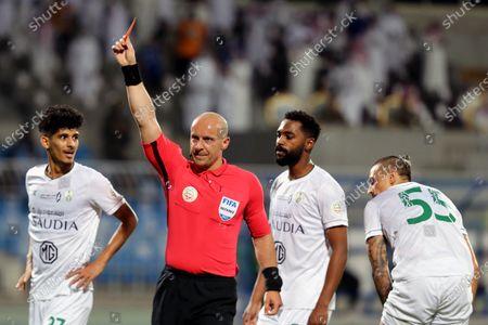 Polish referee Szymon Marciniak (2-L) issues a red card to Al-Ahli's Motaz Hawsawi (not pictured) during the Saudi Professional League soccer match between Al-Hilal and Al-Ahli at Prince Faisal Bin Fahd Stadium, Riyadh, Saudi Arabia, 19 May 2021.