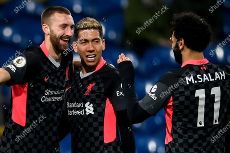 Liverpool's Nathaniel Phillips (L) celebrates with his teammates Roberto Firmino (C) and Mohamed Salah (R) after scoring the 2-0 lead during the English Premier League soccer match between Burnley FC and Liverpool FC in Burnley, Britain, 19 May 2021.