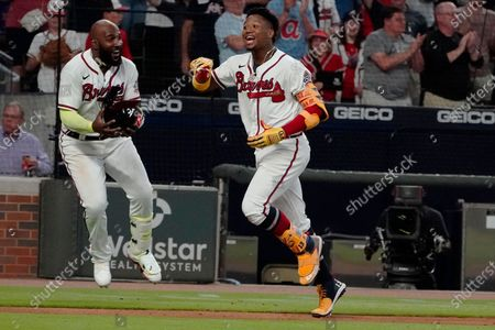 Atlanta Braves' Ronald Acuna Jr. (13), right, runs past Marcell Ozuna as he rounds the bases after hitting a walk-off home run in the ninth inning to defeat the New York Mets in a baseball game, in Atlanta