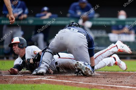 Baltimore Orioles' Ryan Mountcastle, bottom, is tagged out by Tampa Bay Rays catcher Mike Zunino on a fielder's choice ground ball hit by Cedric Mullins during the second inning of a baseball game, in Baltimore