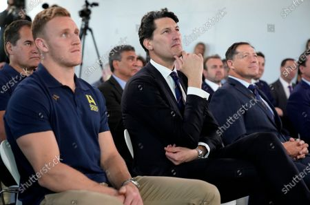 Former Australian rugby Rugby World Cup winning captain John Eales, center, watches a media event in Sydney where Australia formally announced its bid to host the 2027 Rugby World Cup . It would be the third time the sport's showcase event would be held in the country