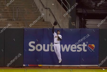 Oakland Athletics left fielder Seth Brown catches a fly ball hit by Houston Astros' Jose Altuve during the ninth inning of a baseball game in Oakland, Calif