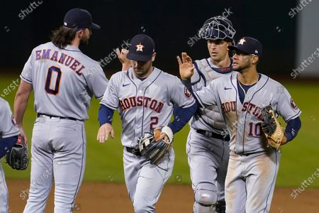 Houston Astros' Kent Emanuel, from left, celebrates with Alex Bregman, Jason Castro and Yuli Gurriel after the Astros defeated the Oakland Athletics 8-1 in a baseball game in Oakland, Calif