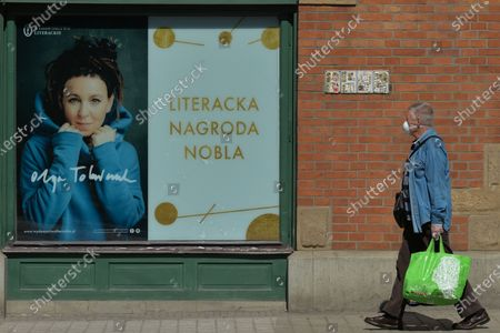 A person wearing a protective mask passes in front of an image of the 2020 Nobel Prize in Literature Olga Tokarczuk.On Wednesday, April 8, 2020, in Krakow, Poland.