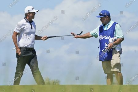 Matt Jones, left, hands his putter to his caddie on the 14th hole during the first round of the PGA Championship golf tournament on the Ocean Course, in Kiawah Island, S.C