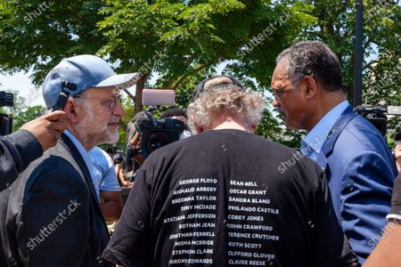Jerry Greenfield (left) and Ben Cohen (center), co-founders of Ben & Jerry's Ice Cream, speak with Rev. Jesse Jackson (right) during his surprise visit to an event urging an end to qualified immunity for police.