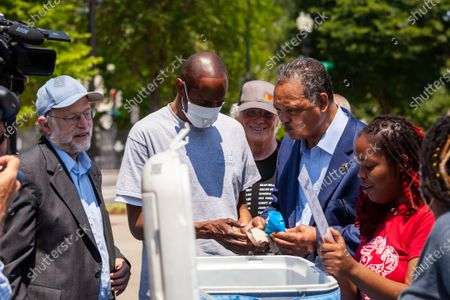 Rev. Jesse Jackson (center right) enjoys an ice cream sandwich with Jerry Greenfield (left) and Ben Cohen (center back), co-founders of Ben & Jerry's Ice Cream, during his surprise visit to an event urging an end to qualified immunity for police.