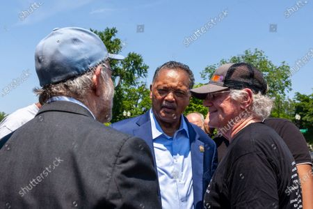 Jerry Greenfield (left) and Ben Cohen (right), co-founders of Ben & Jerry's Ice Cream, speak with Rev. Jesse Jackson (center) during his surprise visit to an event urging an end to qualified immunity for police in front of the Supreme Court.