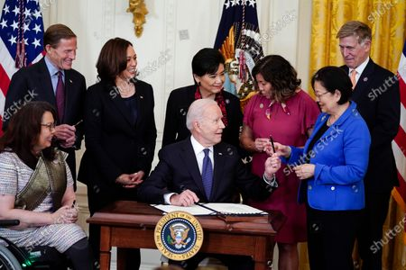 President Joe Biden hands out a pen to Sen. Mazie Hirono, D-Hawaii, after signing the COVID-19 Hate Crimes Act, in the East Room of the White House, in Washington