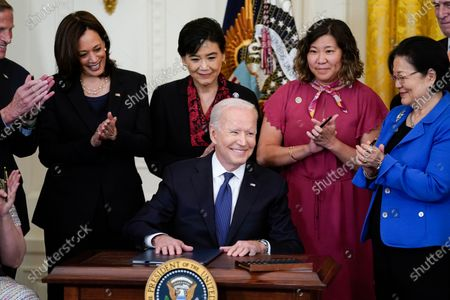 President Joe Biden smiles after signing the COVID-19 Hate Crimes Act, in the East Room of the White House, in Washington. Clockwise from left, Sen. Tammy Duckworth, R-Ill., Sen. Richard Blumenthal, D-Conn., Vice President Kamala Harris, Rep. Judy Chu, D-Calif., Rep. Grace Meng, D-N.Y., Rep. Don Beyer, D-Va., and Sen. Mazie Hirono, D-Hawaii