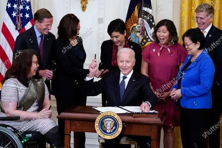 President Joe Biden hands out a pen after signing the COVID-19 Hate Crimes Act, in the East Room of the White House, in Washington. Clockwise from left, Sen. Tammy Duckworth, R-Ill., Sen. Richard Blumenthal, D-Conn., Vice President Kamala Harris, Rep. Judy Chu, D-Calif., Rep. Grace Meng, D-N.Y., Rep. Don Beyer, D-Va., and Sen. Mazie Hirono, D-Hawaii
