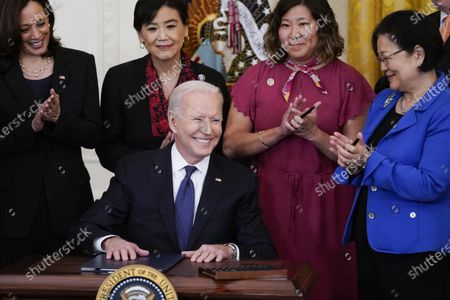 President Joe Biden smiles after signing the COVID-19 Hate Crimes Act, in the East Room of the White House, in Washington. Top row from left, Vice President Kamala Harris, Rep. Judy Chu, D-Calif., Rep. Grace Meng, D-N.Y., and Sen. Mazie Hirono, D-Hawaii