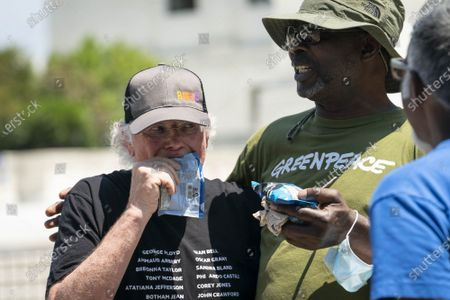 """Ben Cohen, left, co-founder of Ben & Jerry's Ice Cream, eats ice cream outside of the Supreme Court of the United States on Capitol Hill in Washington, DC on Thursday, May 20, 2021. Cohen and Greenfield held a news conference to give out ice cream and """"demand Congress pass meaningful police reform and end qualified immunity."""""""