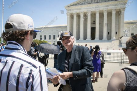 """Ben Cohen, co-founder of Ben & Jerry's Ice Cream, hands out brochures outside of the Supreme Court of the United States on Capitol Hill in Washington, DC on Thursday, May 20, 2021. Cohen and Jerry Greenfield held a news conference to give out ice cream and """"demand Congress pass meaningful police reform and end qualified immunity."""""""