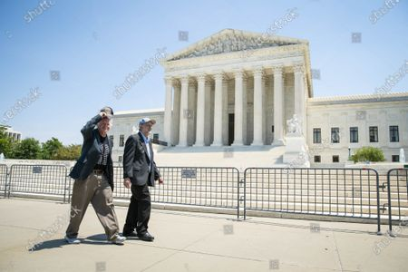 """Ben Cohen, left, and Jerry Greenfield, right, co-founders of Ben & Jerry's Ice Cream, walk past the Supreme Court of the United States after a news conference on Capitol Hill in Washington, DC on Thursday, May 20, 2021. Cohen and Greenfield held an event to give out ice cream and """"demand Congress pass meaningful police reform and end qualified immunity."""""""