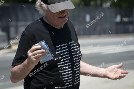 """Stock Photo of Ben Cohen, left, co-founder of Ben & Jerry's Ice Cream, eats ice cream outside of the Supreme Court of the United States on Capitol Hill in Washington, DC on Thursday, May 20, 2021. Cohen and Greenfield held a news conference to give out ice cream and """"demand Congress pass meaningful police reform and end qualified immunity."""""""