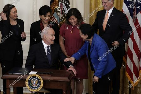 United States President Joe Biden chats with US Senator Mazie Hirono (Democrat of Hawaii) before signing the COVID-19 Hate Crimes Act into law in the East Room at the White House in Washington.