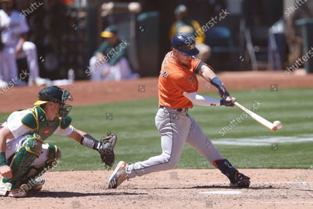 Houston Astros Alex Bregman (R) hits an RBI double off Oakland Athletics relief pitcher Burch Smith as Oakland Athletics catcher Sean Murphy (L) looks on during the seventh  inning of their MLB game at RingCentral Coliseum in Oakland, California, USA, 20 May 2021.