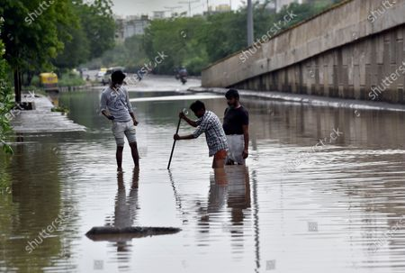 MCG workers clearing a drain to pump water out of a waterlogged stretch, near Subhash Chowk, on May 20, 2021 in Gurugram, India. Gurugram on Wednesday night witnessed record rainfall under the impact of Cyclone Tauktae. The heavy downpour led to waterlogging in several parts of the city.