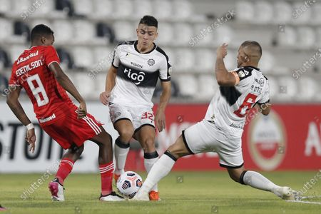 Edenilson of Brazil's Internacional, left, fights for the ball with Braian Ojeda, center, and Richard Ortiz of Paraguay's Olimpia during a Copa Libertadores soccer match at Manuel Ferreira stadium in Asuncion, Paraguay