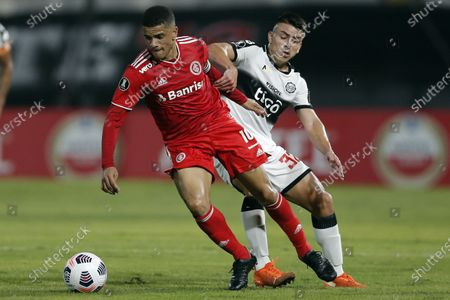 Taison of Brazil's Internacional, left, fights for the ball with Braian Ojeda of Paraguay's Olimpia during a Copa Libertadores soccer match at Manuel Ferreira stadium in Asuncion, Paraguay