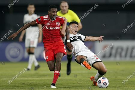 Victor Cuesta of Brazil's Internacional, left, fights for the ball with Braian Ojeda of Paraguay's Olimpia during a Copa Libertadores soccer match at Manuel Ferreira stadium in Asuncion, Paraguay