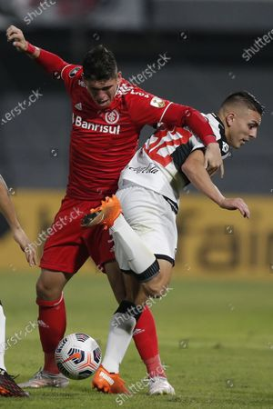 Carlos Palacios of Brazil's Internacional, left, fights for the ball with Braian Ojeda of Paraguay's Olimpia during a Copa Libertadores soccer match at Manuel Ferreira stadium in Asuncion, Paraguay