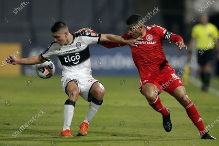 Braian Ojeda of Paraguay's Olimpia, let, fights for the ball with Taison of Brazil's Internacional during a Copa Libertadores soccer match at Manuel Ferreira stadium in Asuncion, Paraguay
