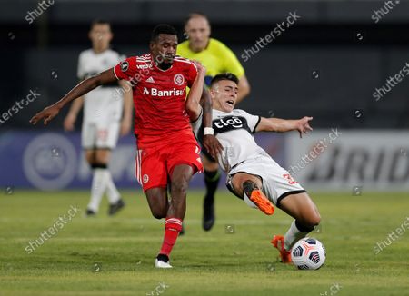 Braian Oscar Ojeda (R) of Olimpia in action against Victor Leandro Cuesta (L) of Internacional during the Copa Libertadores group B soccer match between Olimpia and Internacional at the Manuel Ferreira Stadium, in Asuncion, Paraguay, 20 May 2021.