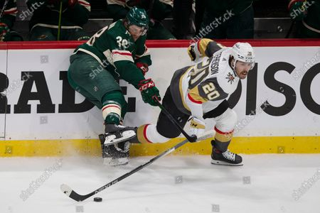 Vegas Golden Knights' Chandler Stephenson (20) gains control of the puck against Minnesota Wild's Ryan Hartman (38) during the first period in Game 3 of a first-round NHL hockey playoff series, in St. Paul, Minn