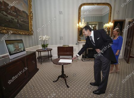 Stock Image of Britain's Queen Elizabeth II appears on a screen by videolink from Windsor Castle, where she is in residence, during a virtual audience to receive His Excellency Dr Cesar Rodriguez-Zavalla, the Ambassador of Uruguay, and his wife Maria Angelica Algorta-Carrau, at Buckingham Palace, London