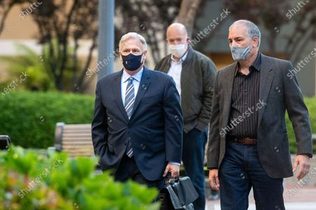 Apple fellow Phil Schiller, left, enters the Ronald V. Dellums building in Oakland, Calif., to testify in a federal court case brought by Epic Games on . Epic, maker of the video game Fortnite, charges that Apple has transformed its App Store into an illegal monopoly