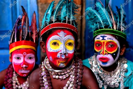 This family of performers have their faces painted in an extraordinary range of bright colours as part of their act.  The Bahrupi artist and his children in East Burdwan, India, stage performances which focuses on the theme of different tribal cultures.  Bahurupi artists use face paint to transform into different characters during the shows and focus on myths, legends and religious characters in their shows.  This group are returning to work now after a lengthy hiatus due to the coronavirus pandemic.