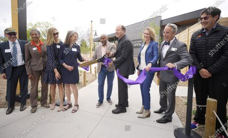 Denver Mayor Michael Hancock, fifth from left, and Colorado Governor Jared Polis, sixth from left, cut the ribbon as board members look on during a ceremony to mark the public opening of the new animal hospital serving the Denver Zoo's 3,000 residents, in Denver. A grant from the Helen and Arthur E. Johnson Foundation combined with funds from a 2017 city bond issue were used to build the state-of-the-art hospital, which offers visitors a chance to watch procedures through the viewing windows in the lobby