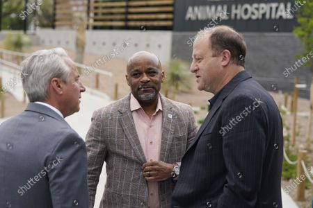 Denver Mayor Michael Hancock, center, chats with Colorado Governor Jared Polis, right, and Bert Vescolani, president and chief executive officer of the Denver Zoo, during a ceremony to mark the public opening of the new animal hospital serving the zoo's 3,000 residents, in Denver. A grant from the Helen and Arthur E. Johnson Foundation combined with funds from a 2017 bond issue were used to build the state-of-the-art hospital, which offers visitors a chance to watch procedures through the viewing windows in the lobby