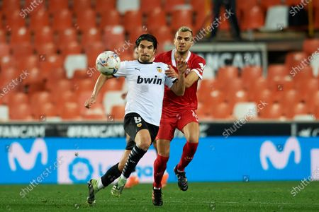 Carlos Soler of Valencia and Joan Jordan of Sevilla compete for the ball during the La Liga Santander match between Valencia CF and Sevilla FC at Estadio Mestalla on December 22, 2020 in Valencia, Spain. Sporting stadiums around Spain remain under strict restrictions due to the Coronavirus Pandemic as Government social distancing laws prohibit fans inside venues resulting in games being played behind closed doors.