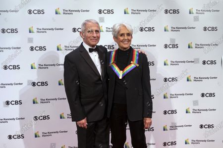 Kennedy Center honoree Joan Baez poses with Dr. Anthony Fauci, center, director of the National Institute of Allergy and Infectious Diseases, during the 43nd Annual Kennedy Center Honors at The Kennedy Center, in Washington