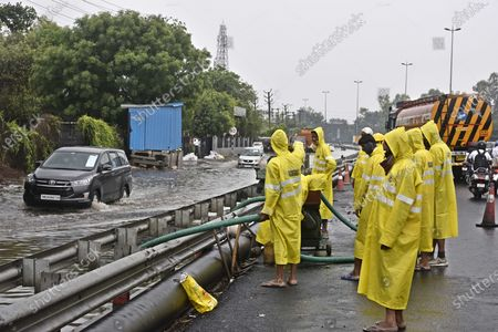 MCG workers clear the logged rain water at (Service lane ) at Narsingpur alongside NH 48 , on May 21, 2021 in Gurugram, India. Heavy rains lashed Delhi-NCR on May 19 as impact from Tauktae Cyclone.