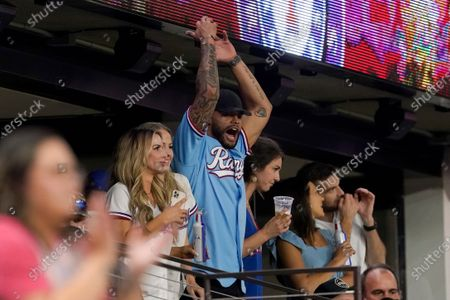 Dallas Cowboys quarterback Dak Prescott waves his arms motivating fans and cheering on the Texas Rangers in the 10th inning of the Rangers' baseball game against the Houston Astros in Arlington, Texas