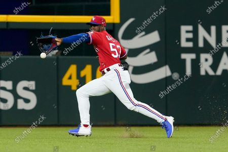 Texas Rangers center fielder Adolis Garcia chases down a single hit by Houston Astros' Jason Castro during the second inning of a baseball game in Arlington, Texas