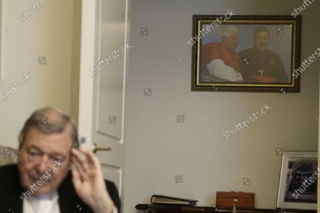 Picture of Pope Benedict XVI and Australian Cardinal George Pell taken in Sydney during the 2008 World Youth Day hangs on a wall of Cardinal Pell's home while he is interviewed by The Associated Press at the Vatican, . Pell, who was convicted and then acquitted of sex abuse charges in his native Australia, is spending his newfound freedom in Rome