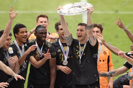 Niklas Suele of FC Bayern Muenchen lifts the Bundesliga Meisterschale Trophy in celebration with his players following the Bundesliga match between FC Bayern Muenchen and FC Augsburg at Allianz Arena in Munich, Germany, 22 May 2021 (issued 23 May 2021).