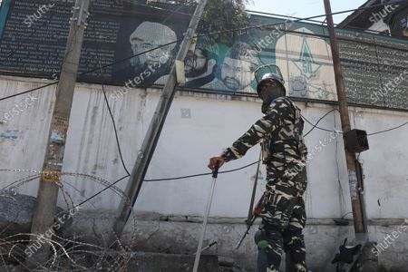Indian forces stand alert outside the residence of Pro-freedom leader Mirwaiz Umar Farooq during the strictest Covid-19 curfew on the anniversary of the assasination of two Pro-Freedom leaders in Srinagar, Indian Administered Kashmir on 21 May 2021.