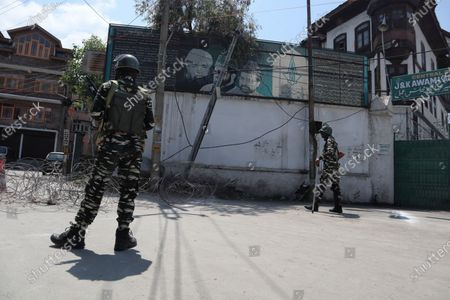Stock Image of Indian forces stand alert outside the residence of Pro-freedom leader Mirwaiz Umar Farooq during the strictest Covid-19 curfew on the anniversary of the assasination of two Pro-Freedom leaders in Srinagar, Indian Administered Kashmir on 21 May 2021.